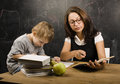 Little cute boy with young teacher in classroom studying at blackboard smiling doing homework Royalty Free Stock Photos