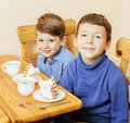 Little cute boys eating dessert on wooden kitchen. home interior. smiling adorable friendship together forever friends Royalty Free Stock Photo