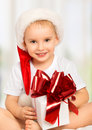 Little cute child boy in a christmas hat with a gift box ribbon Stock Image
