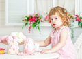 Little cute curly girl in a pink dress with lace and polka dots sitting at the table and eating different sweets.