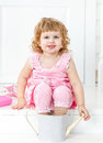 Little cute curly girl in a pink dress with polka dots smiling, sitting on the white porch Provence style