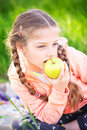 Little cute girl on a background of green grass with an apple Royalty Free Stock Photo