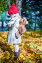Little cute girl with a backpack-bear walks in the
