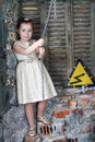 Little cute girl in beautiful dress hold by big metal chain very old house Stock Image