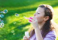 Little cute girl blowing soap bubbles outdoors summer Royalty Free Stock Photos