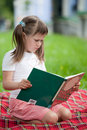 Little cute girl with book on plaid in park Royalty Free Stock Photography