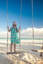 Little cute girl in dress riding a seesaw on the beach this image has attached release Royalty Free Stock Photo