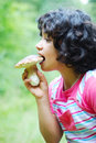 A little cute girl is eating mushroom Royalty Free Stock Photo