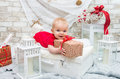 Little cute girl five months on the eve of Christmas with a gift Royalty Free Stock Photo