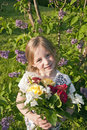 Little cute girl with flowers in garden Royalty Free Stock Image