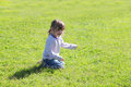 Little cute girl in jeans sitting on grass Royalty Free Stock Photo
