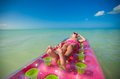 Little cute girl on pink air bed sunbathe in caribbean sea Stock Image