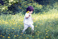 Little cute girl playing in the meadow with dandelions Royalty Free Stock Photo