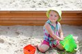 Little cute girl playing in sandbox child adorable blonde toddler enjoying hot sunny summer day at the playground sitting inside Stock Photo