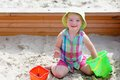 Little cute girl playing in sandbox child adorable blonde toddler enjoying hot sunny summer day at the playground sitting inside Royalty Free Stock Image