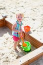 Little cute girl playing in sandbox child adorable blonde toddler enjoying hot sunny summer day at the playground sitting inside Stock Photos