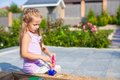 Little cute girl playing at the sandbox with toys Royalty Free Stock Photo