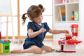 Little cute girl playing with utensil toys. Toddler kid in a playroom. Kid sitting on floor and cook in toy kitchen. Royalty Free Stock Photo