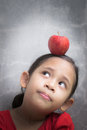 Little cute girl with red apple on hers head looking up Royalty Free Stock Photos