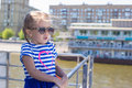 Little cute girl relaxing on a luxury ship sailing in the big city deck of Stock Image