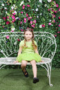 Little cute girl sits on bench and swing legs near verdant hedge Stock Images