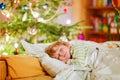Little cute kid boy sleeping under Christmas tree Royalty Free Stock Photo