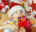 Little cute kid in santas red hat with handmade gifts, toys vintage wooden, warm winter Royalty Free Stock Photo