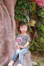 Little cute lovely girl Chinese child smile laugh play by a tree hold lollipop at summer park nature happiness childhood Royalty Free Stock Photo