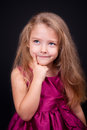 Little cute pensive girl in a bright pink dress Royalty Free Stock Photo