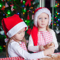 Little cute sisters bake gingerbread cookies for christmas in santa hat this image has attached release Stock Image