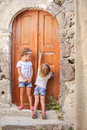 Little cute sisters near old door in Greek village Royalty Free Stock Photo