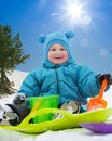 Little cute toddler on snow day close up of happy sitting sled in in winter Stock Image
