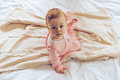Little cutie in bed top view baby girl looking at camera while sitting on blanket Stock Images