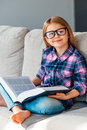 Little cutie with book cheerful girl in glasses holding and looking at camera smile while sitting on the couch in lotus position Stock Photo