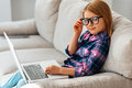 Little cutie with laptop beautiful girl in glasses using her and looking at camera while sitting on the couch at home Royalty Free Stock Images