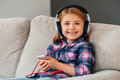 Little cutie loves music cheerful girl in headphones holding smart phone and looking at camera with smile while sitting on the Royalty Free Stock Photography