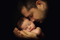 Little 15 days old baby lying securely on his Dad`s arms, against a black background Royalty Free Stock Photo