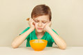 Little discontented boy does not want to eat porridge Royalty Free Stock Photo