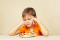 Little displeased boy does not want to eat pasta with cutlet a Royalty Free Stock Image