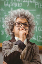 Little Einstein thinking in front of chalkboard in a classroom Royalty Free Stock Photo