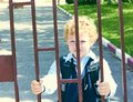 Little elementary school student stands next to his school holding hands for the school fence. Royalty Free Stock Photo
