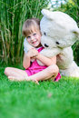 Little elfin girl sittinging in the grass with large teddy bear Royalty Free Stock Photo