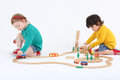 Little enthusiastic girl and boy play with trains wooden railway on floor on white background Stock Images