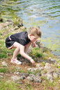 Little explorer special needs child exploring on her own nature by a pond Royalty Free Stock Photography