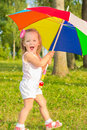 Little fun beautiful girl walks in the Park with colorful umbrella