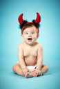 Little funny baby devil horns blue background Stock Photography