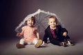 Little funny boy and girl under umbrella