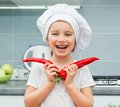 Little funny girl in a cap chef in the kitchen with pepper Royalty Free Stock Photos