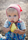 Little funny girl eates a pear Stock Photography