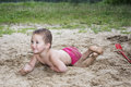 Little funny girl lying on the sand near the lake in summer and Royalty Free Stock Photo